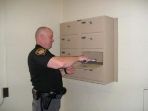 Officers must lock their weapons inside a lockbox before entering the booking area.